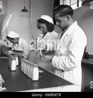 1950s, historical, male and female lab technicians in white coats working at a diary checking samples of milk taken - Stock Photo
