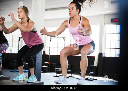 Determined young women doing jump squats in exercise class - Stock Photo