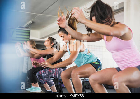 Young women doing jump squats in exercise class - Stock Photo