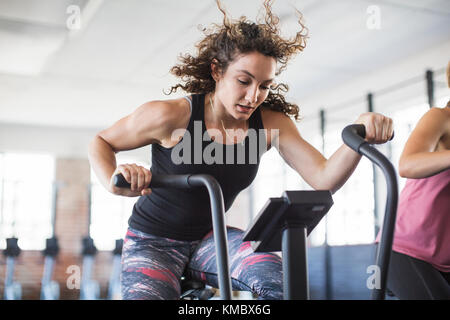 Determined young woman riding elliptical bike in gym - Stock Photo