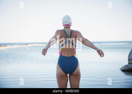 Female open water swimmer stretching at ocean - Stock Photo