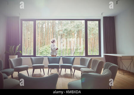 Pensive woman looking out windows at tress in group therapy room - Stock Photo