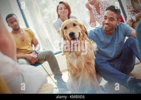 Man petting dog in group therapy session - Stock Photo