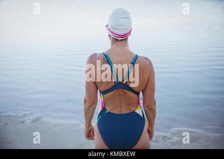 Female open water swimmer standing on ocean beach - Stock Photo