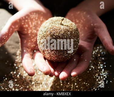 Hands cupping golden glitter apple - Stock Photo