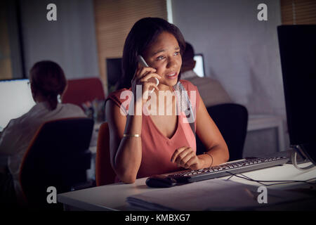 Businesswoman working late,talking on smart phone at computer in dark office - Stock Photo