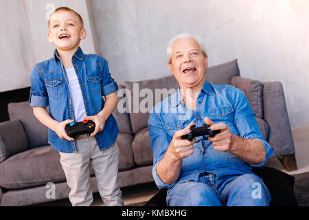 Happy cheerful grandfather playing video games - Stock Photo