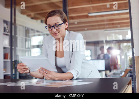 Female design professional reviewing photograph proofs in office - Stock Photo