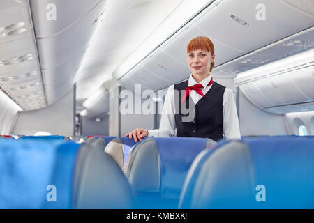 Portrait confident female flight attendant on airplane - Stock Photo