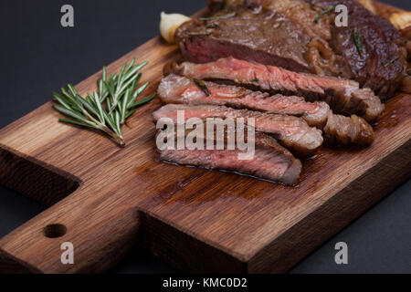 Grilled ribeye steak of marble beef closeup with spices on a wooden Board. Juicy steak medium sliced and ready to - Stock Photo