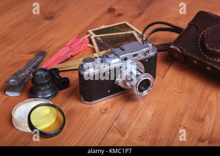 Vintage old photo-camera, leather case and other photo accessories on wooden background. - Stock Photo