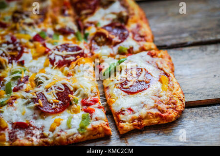 Square Pepperoni Pizza On Rustic Wooden Background - Stock Photo