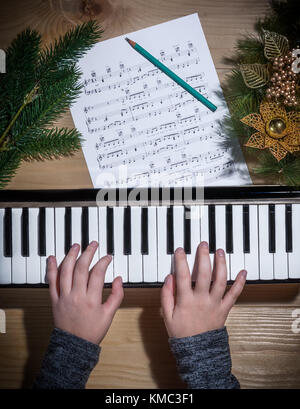 Young hands of a girl playing on a keyboard with Christmas decorations on a wooden table - Stock Photo