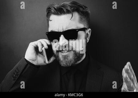 A businessman in a black suit swears by phone with his subordinates. A man in sunglasses speaks on the phone, gesturing - Stock Photo
