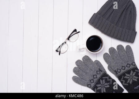 Men's winter casual outfits with coffee cup and eyeglasses on wooden background - Stock Photo