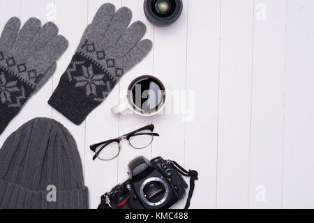 Men's winter casual outfits with camera, coffee cup and eyeglasses on wooden background - Stock Photo