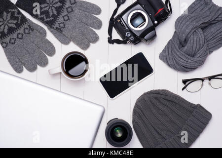 Men's winter casual outfits with camera, coffee cup, laptop, smartphone and eyeglasses on wooden background - Stock Photo