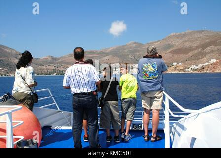 Passengers stand at the bow of Dodekanisos Seaways catamaran ferry Dodekanisos Express on arrival at Livadia harbour - Stock Photo