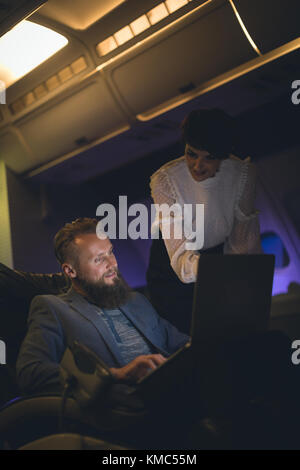 Businessman discussing over laptop with female executive - Stock Photo