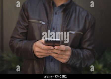 Man using mobile phone in chocolate bar - Stock Photo