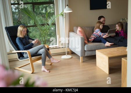 Father using digital tablet with children while mother using mobile phone in living room - Stock Photo