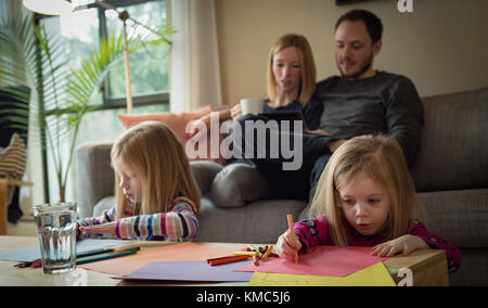 Parents using digital tablet while children drawing a sketch in living room - Stock Photo