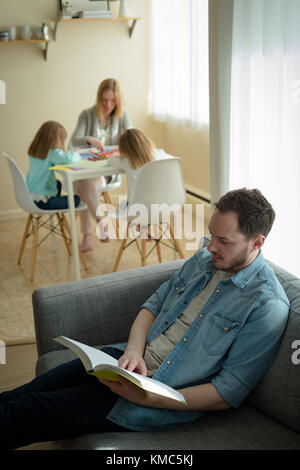 Father reading a book while mother helping her children in studies - Stock Photo