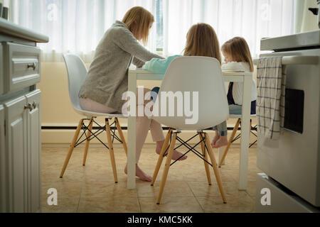 Mother helping her children in studies - Stock Photo