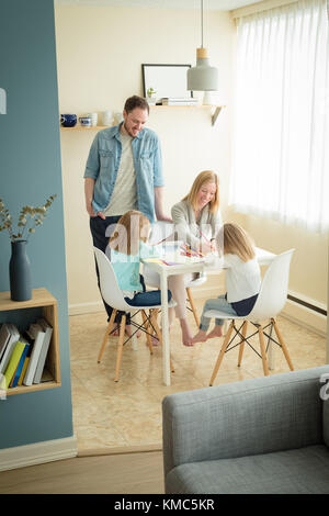 Mother and father helping their children in studies - Stock Photo