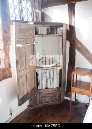 old wooden wash cupboard basin sink closet in corner of english manor house room antique; essex; england; uk - Stock Photo
