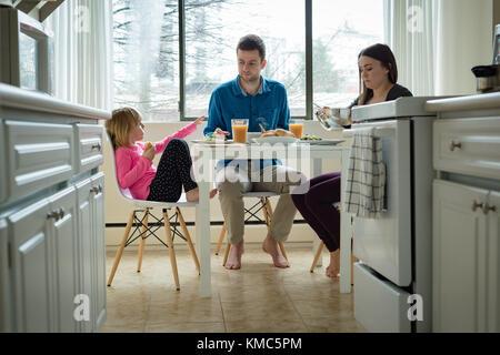 Family having breakfast in kitchen - Stock Photo
