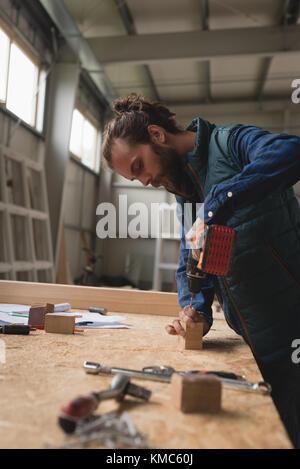 Carpenter making hole in wooden block with screw gun - Stock Photo