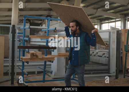 Carpenter carrying wooden plank - Stock Photo