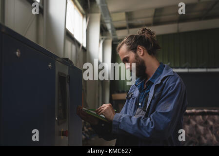 Mechanic maintaining record on clipboard - Stock Photo