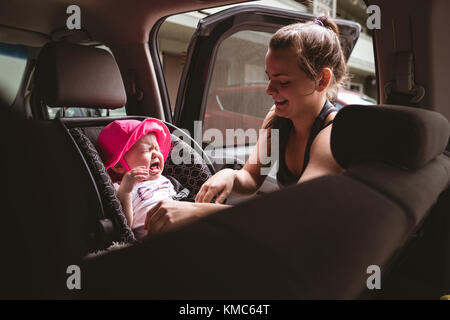 Mother attending her crying baby - Stock Photo