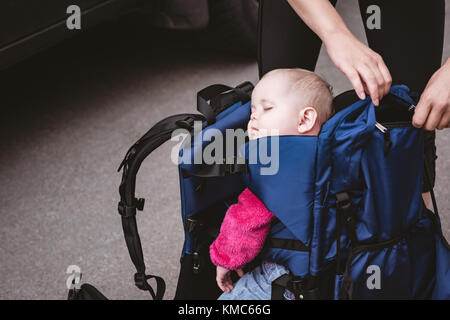 Baby taking a nap in the backpack carrier - Stock Photo