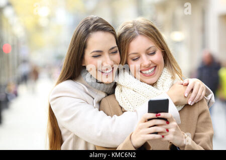 Front view portrait of two cheerful friends watching smart phone content in winter on the street - Stock Photo