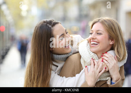 Two happy friends joking and laughing on the street in winter - Stock Photo