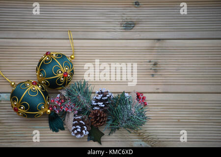 Christmas photography image with red and green bauble decorations and pine cones with branches with snow on rustic - Stock Photo