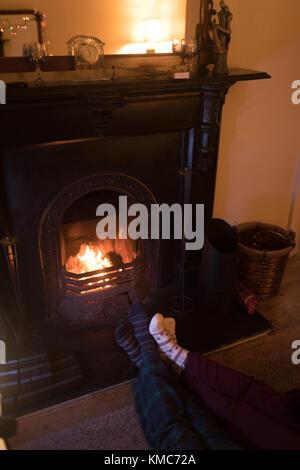 Couple feet in knitted woolen socks warming near burning fireplace - Stock Photo
