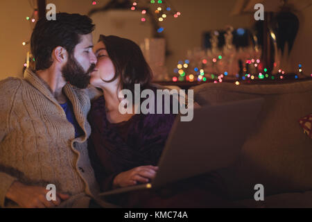 Couple kissing each other while using laptop in living room - Stock Photo