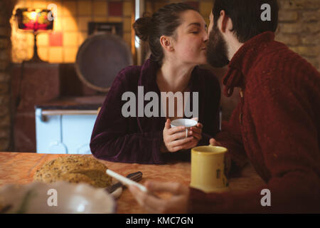 Couple kissing each other while having cup of coffee at home - Stock Photo