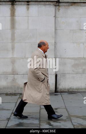 Caucasian man wearing trench coat with hands in pockets walking through Trafalgar Square, London, England, UK - Stock Photo