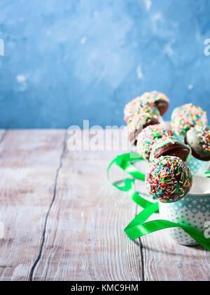 Closeup of colorful chocolate cake pops with sugar sprinkles in small coffee cups on wooden table. Copy space. Vertical - Stock Photo