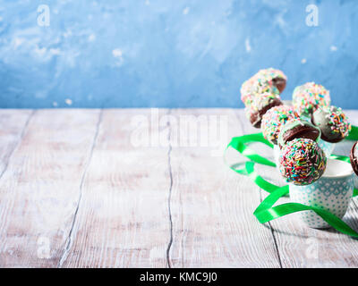 Closeup of colorful chocolate cake pops with sugar sprinkles in small coffee cups on wooden table. Copy space - Stock Photo