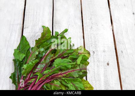 Fresh farm beet leaf bunch on white wood desk - Stock Photo