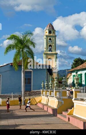 Bell tower of Iglesia y Convento de San Francisco, Plaza Mayor, kids playing soccer, Trinidad Cuba - Stock Photo