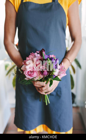Cropped shot of woman holding mixed flower bouquet in hand. Florist with fresh flowers at flower shop. - Stock Photo