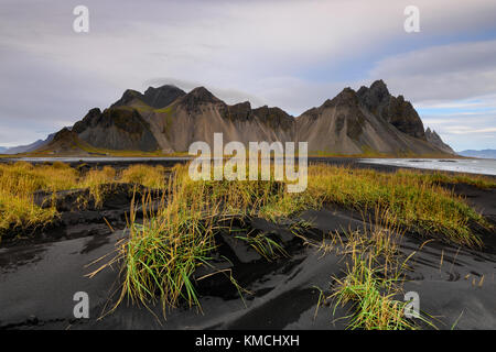 Amazing Vesturhorn mountain landscape in Iceland at sunset. Black sand beach with mountain range background and - Stock Photo