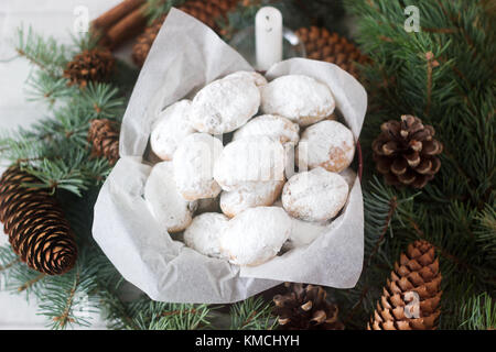 Mini stollen or stollen candy in a tin on a background of fir branches and cones. - Stock Photo
